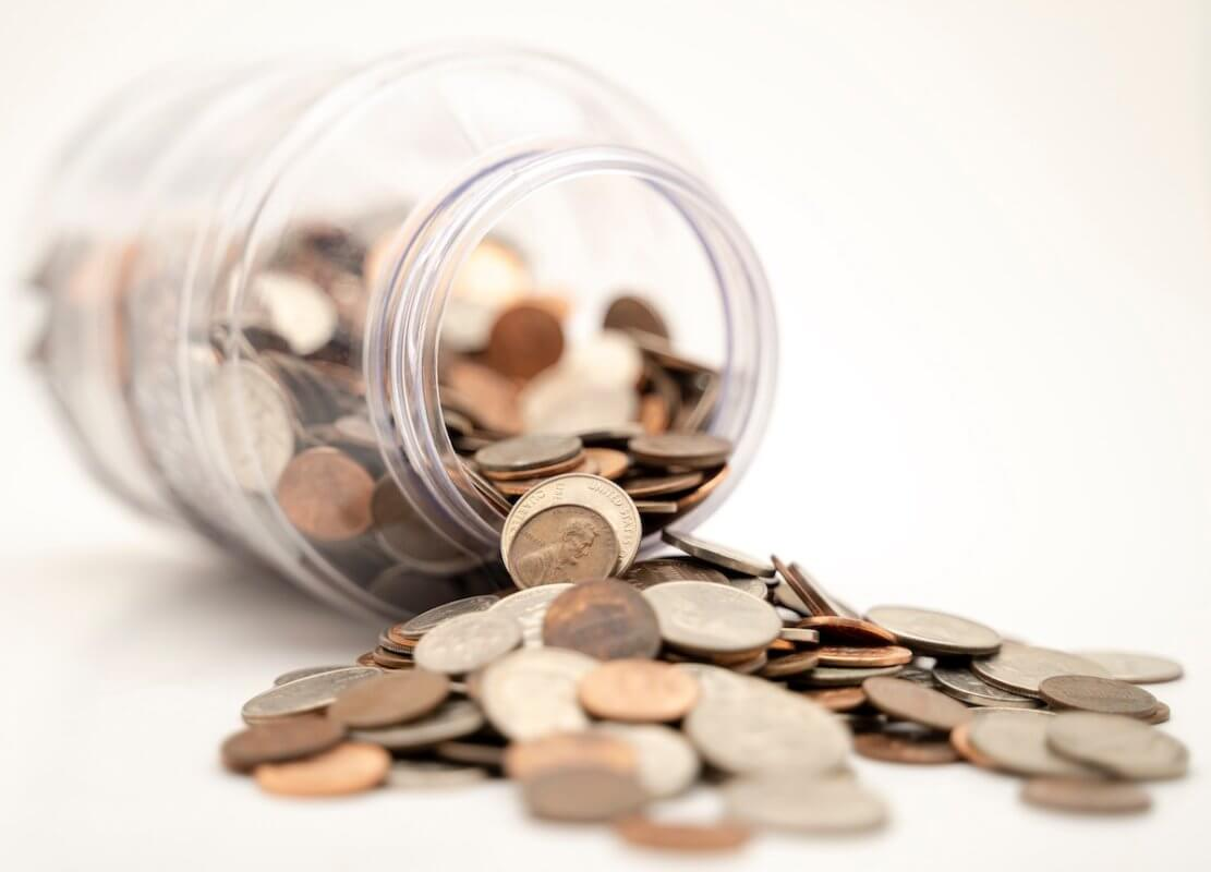 Coins spilling out of a jar in an article about finding funding for your small business.