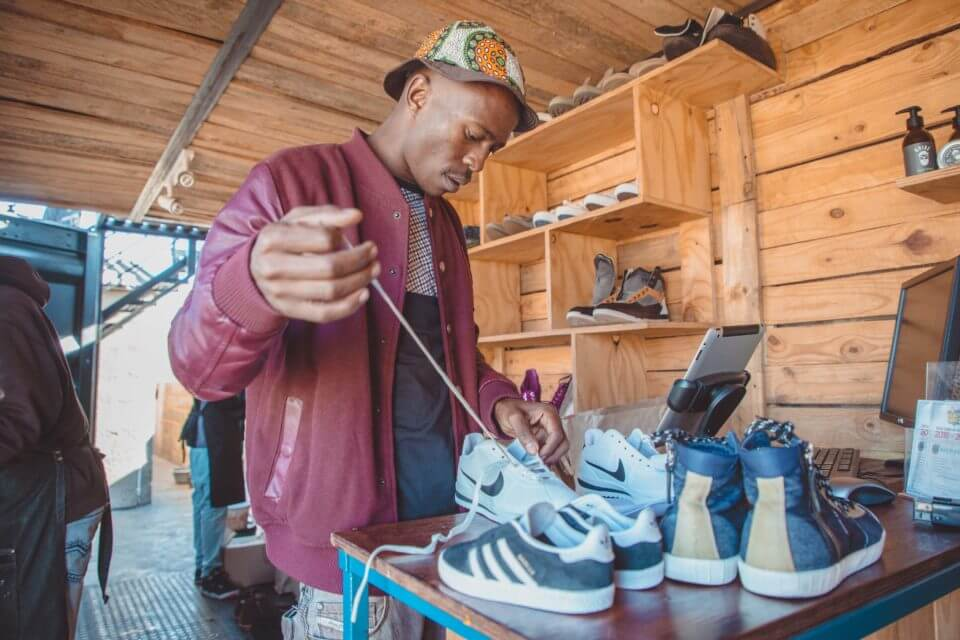 Lethabo lacing a pair of sneakers at Walk Fresh.