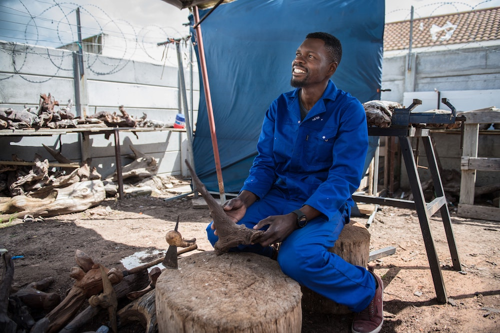 Boniface working in the Unique Driftwood Creations workshop.