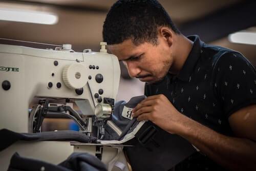 Rodney working on his sewing machine at Ubuntu Baba.