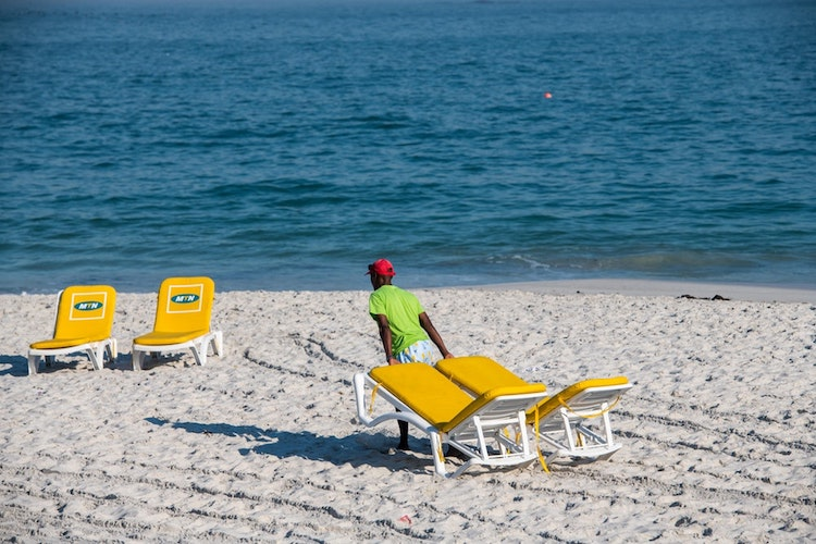 Pulling chairs on a Cape Town beach.