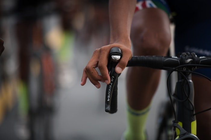 A closeup of a man holding a bicycle's handlebar.