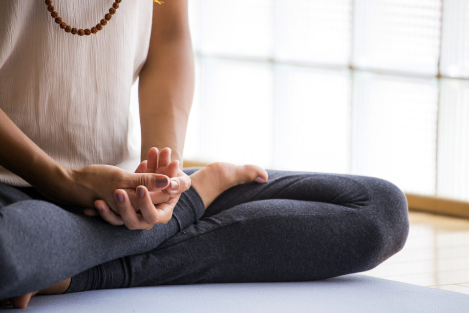 A woman sitting cross legged in article about managing the effects of your business on your health.