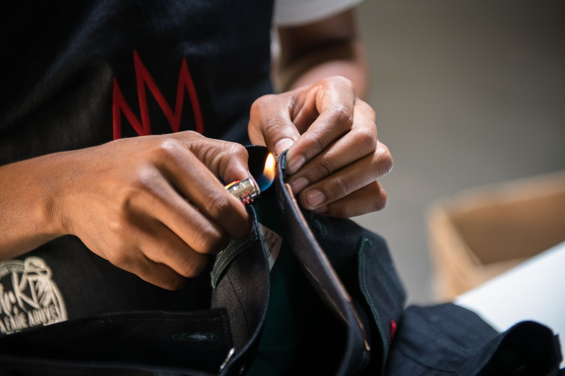 Burning the finishing touches on a pair fo jeans.