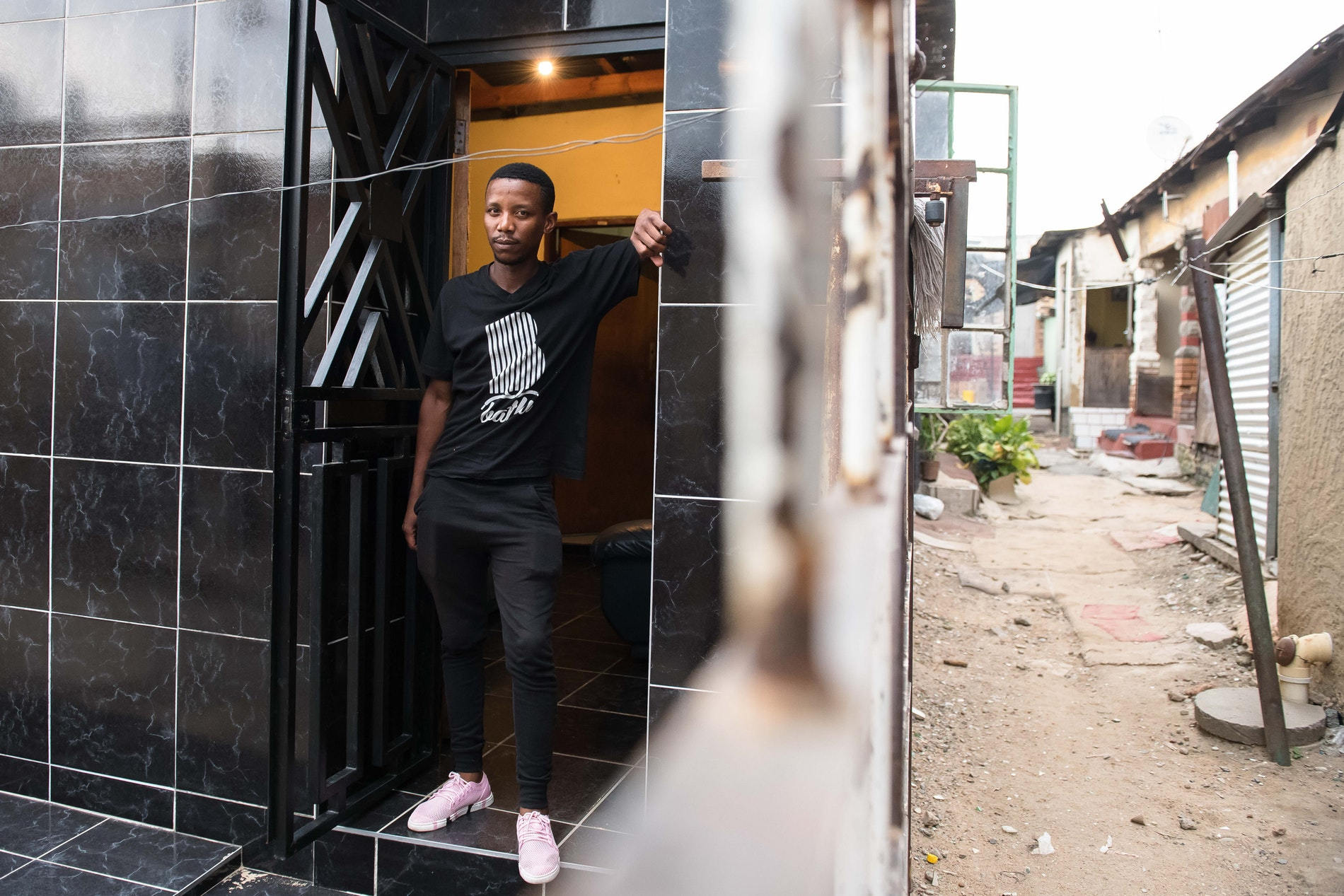 A man standing outside the house where Theo Baloyi started Bathu shoes.