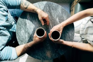 Two people have a cup of coffee in a business mentor meeting.