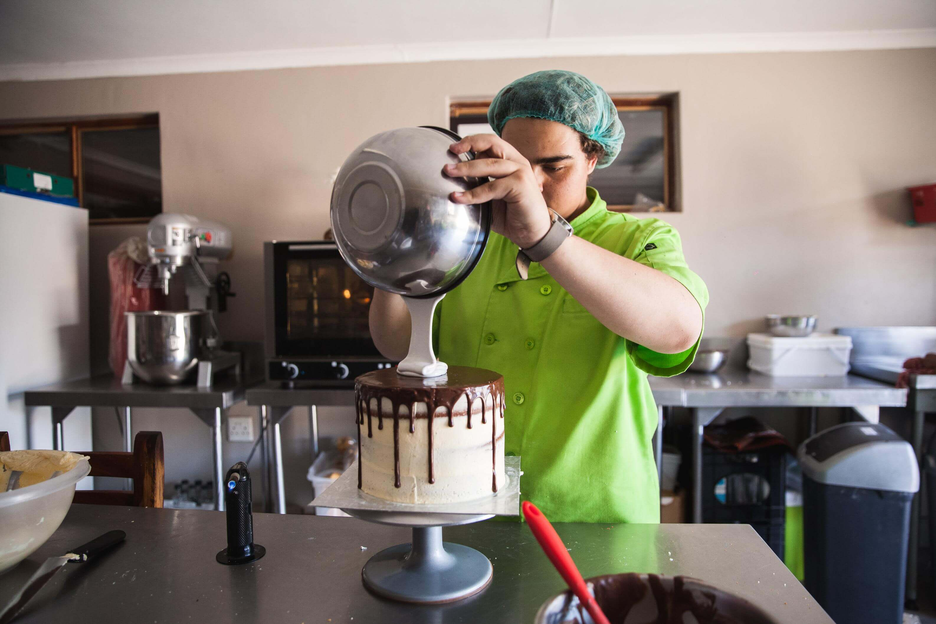 Hermaan of Baking Co in Polokwane pouring icing on a cake.