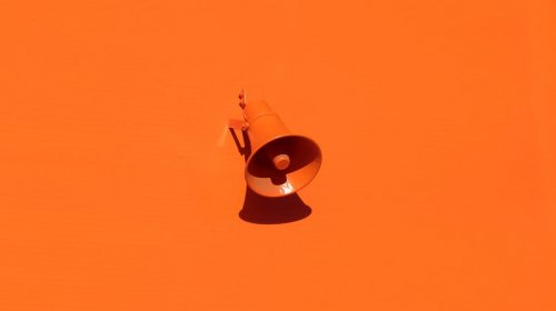 Orange speaker on a wall in an article about marketing trends.