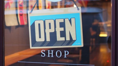 An image of a store open sign in an article about opening a retail store.